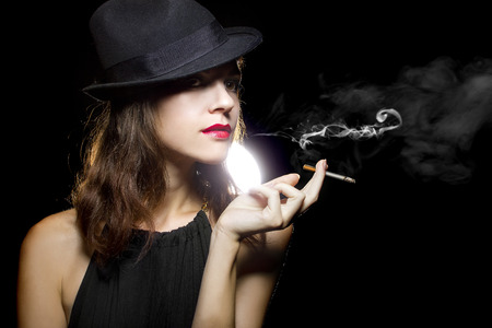 young female in stylish hat smoking a lit cigarette photo