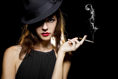 fag: young female in stylish hat smoking a lit cigarette Stock Photo