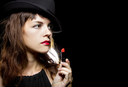 stylish caucasian female putting on red lipstick on black background photo