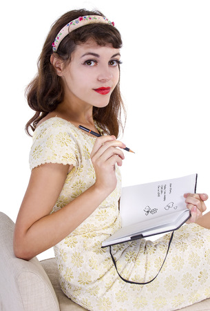 young female writing on a retro style diary with text space photo