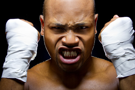 aggresive: portrait of an intense black fighter holding fists up