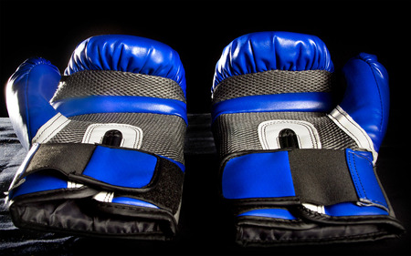 fortitude: boxing gloves or martial arts gear on a black background Stock Photo