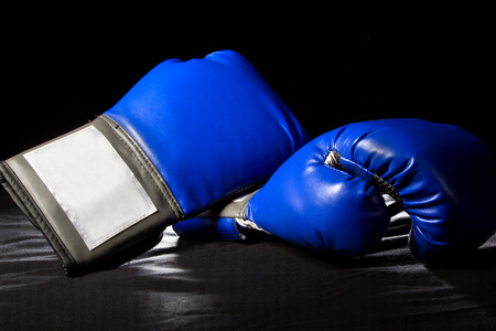 bout: boxing gloves or martial arts gear on a black background Stock Photo