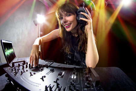 caucasian female dj using a mixer and computer to play mp3s photo