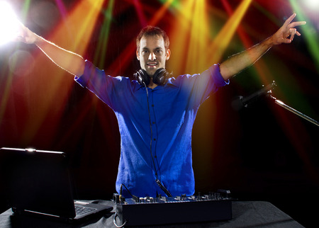 caucasian male dj playing mp3 music with computer and mixer