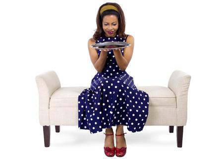 fille noire: jeune fille noire tenant un plateau vide assis sur une chaise longue