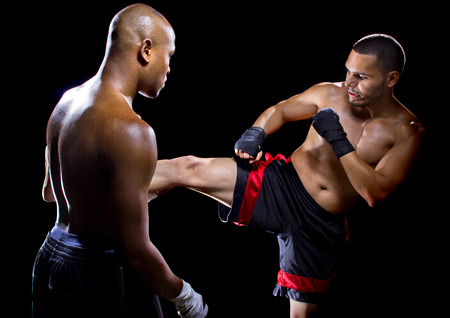 black empowerment: MMA instructor or coach teaching a student how to kick