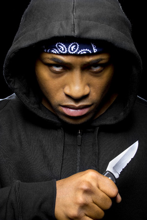 thug wearing a hoodie and holding a knife coming out of the shadows