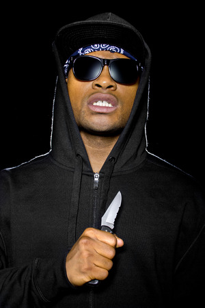 holding a knife: thug wearing a hoodie and holding a knife coming out of the shadows