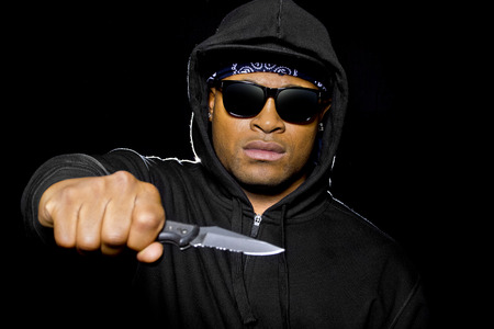 mugging: thug wearing a hoodie and holding a knife coming out of the shadows