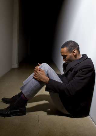 african american male: depressed man who lost faith sitting alone in a dark hallway