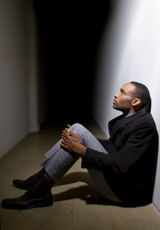 depressed man who lost faith sitting alone in a dark hallway