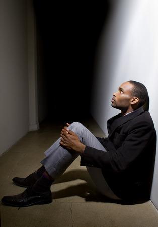 depressieve man die het geloof verloren zit alleen in een donkere gang