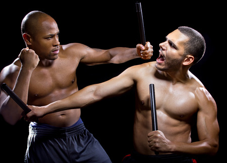 kali: two men sparring with Filipino stick fighting martial arts