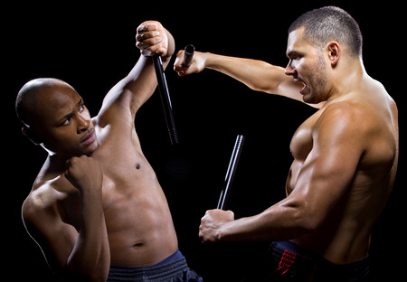weaponry: two men sparring with Filipino stick fighting martial arts