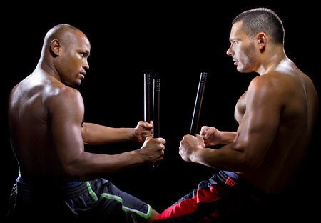 bout: two men sparring with Filipino stick fighting martial arts