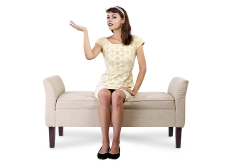 textspace: Stylish retro female sitting on a chaise lounge or sofa on white background