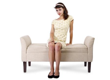 スタイリッシュなレトロ女性 chaise のラウンジや白い背景のソファーに座って