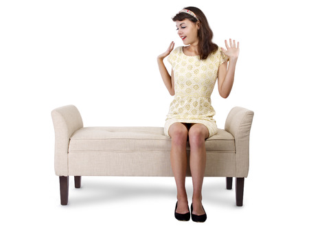 chaise lounge: Stylish retro female sitting on a chaise lounge or sofa on white background