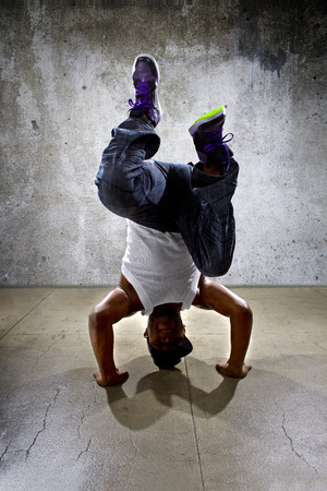 headstand: Inverted black breakdancer doing a headstand or handstand or urban yoga
