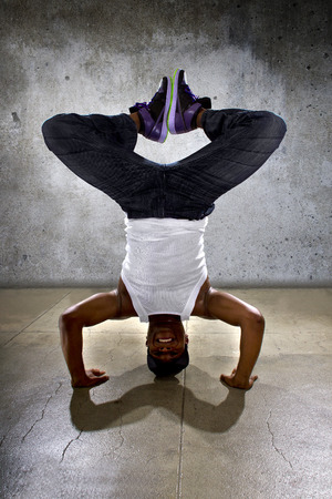 topsyturvy: Inverted black breakdancer doing a headstand or handstand or urban yoga