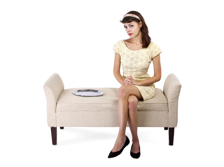reluctant: young female looking unsure sitting next to an empty dessert tray.  empty serving tray for composites Stock Photo