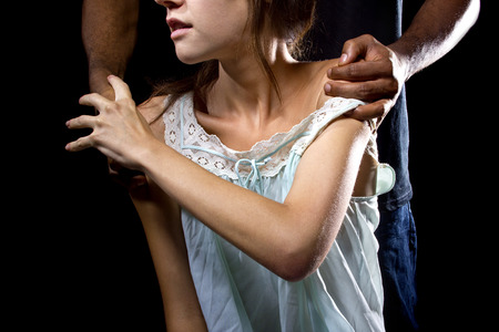 abused: Oppressive man behind a female victim of domestic violence or abuse