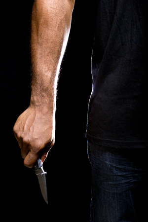 holding a knife: Close up of a robbers hands holding a knife in the shadows Stock Photo