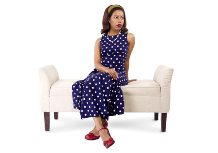 chaise lounge: woman wearing a blue polka dot dress sitting on a vintage chaise lounge