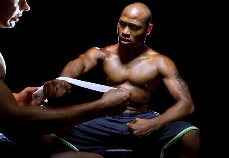 ringside: Motivated MMA fighter or Boxer with trainer applying athletic tape