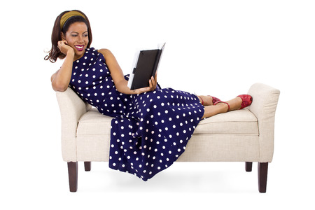 Retro vintage black female reading a book while laying on a chaise photo