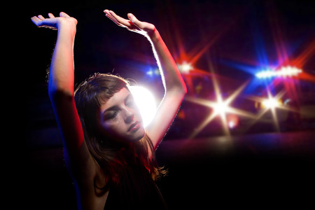 under arrest: young drug intoxicated female holding her hands up while being arrested Stock Photo