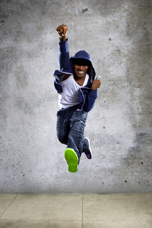 urban dance: Black urban hip hop dancer jumping high on a concrete background