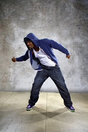 hip hop dance pose: black man wearing a blue hoodie pulling something