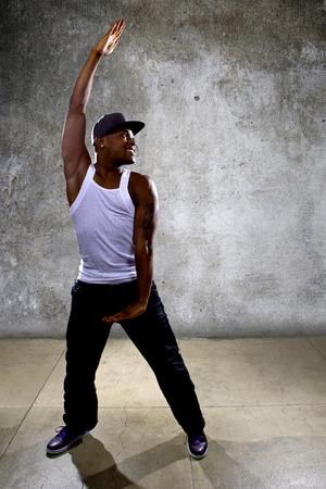 baile hip hop: Hombre negro muscular que presenta la coreograf�a de baile hip hop en el fondo de hormig�n