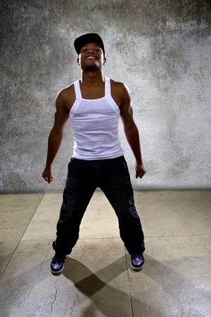 coreografia: Hombre negro muscular que presenta la coreograf�a de baile hip hop en el fondo de hormig�n