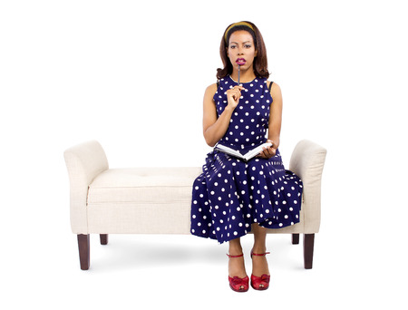 chaise lounge: Vintage style black female author writing and sitting on a chaise lounge