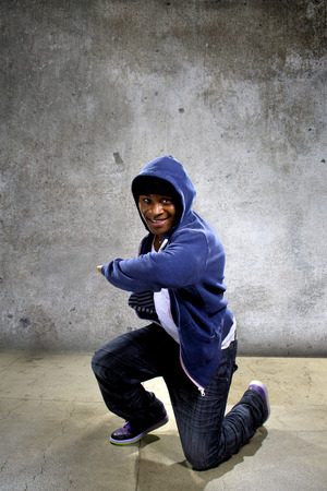hip hop style: young black male dancing hip hop style in an urban setting