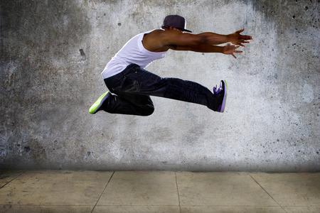 Black urban hip hop danser springt hoog op een concrete achtergrond Stockfoto