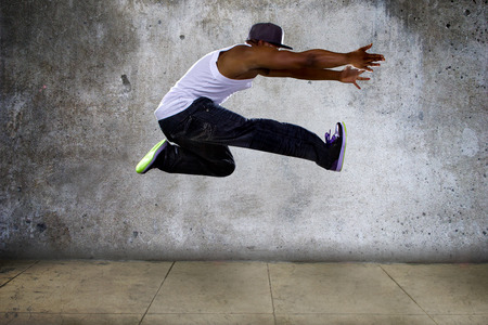 Black urban hip hop dancer jumping high on a concrete background