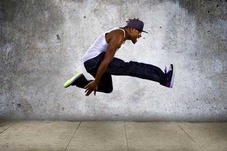 leap: Black urban hip hop dancer jumping high on a concrete background