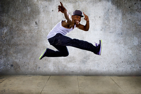 hip hop dancer: Black urban hip hop dancer jumping high on a concrete background