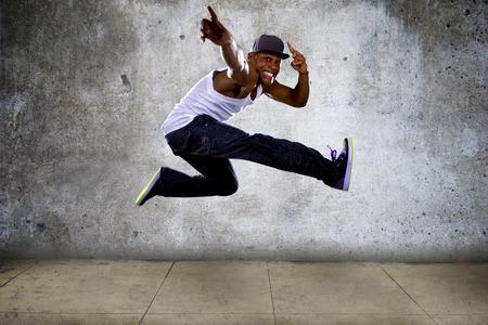 african dance: Black urban hip hop dancer jumping high on a concrete background