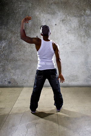 choreographer: Muscular black man posing hip hop dance choreography on concrete background