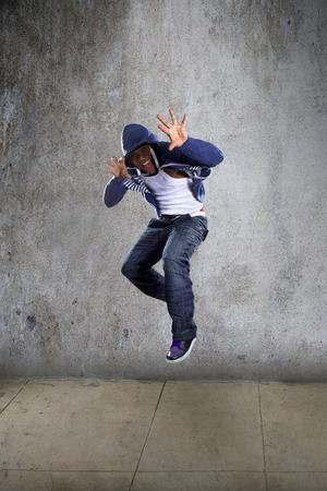hip: Black urban hip hop dancer jumping high on a concrete background