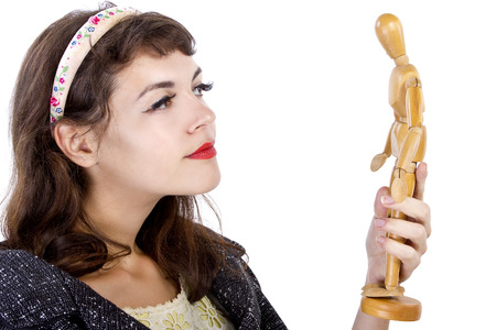 artists dummies: young female holding a wooden figurine and thinking of the perfect man Stock Photo