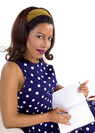Black female in vintage clothing writing on a diary on white background Stock Photo