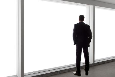 ejecutivos: Hombre de negocios de edad mirando por una ventana de la oficina brillante y pensamiento