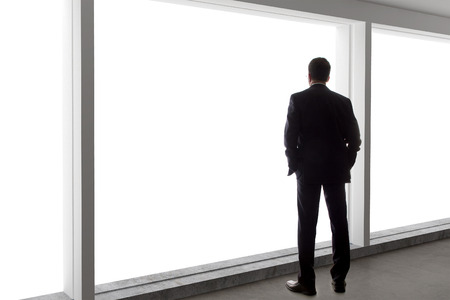 men standing: Middle aged businessman looking out a bright office window and thinking