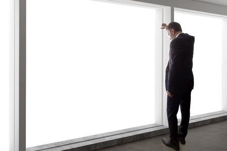 window view: Middle aged businessman looking out a bright office window and thinking
